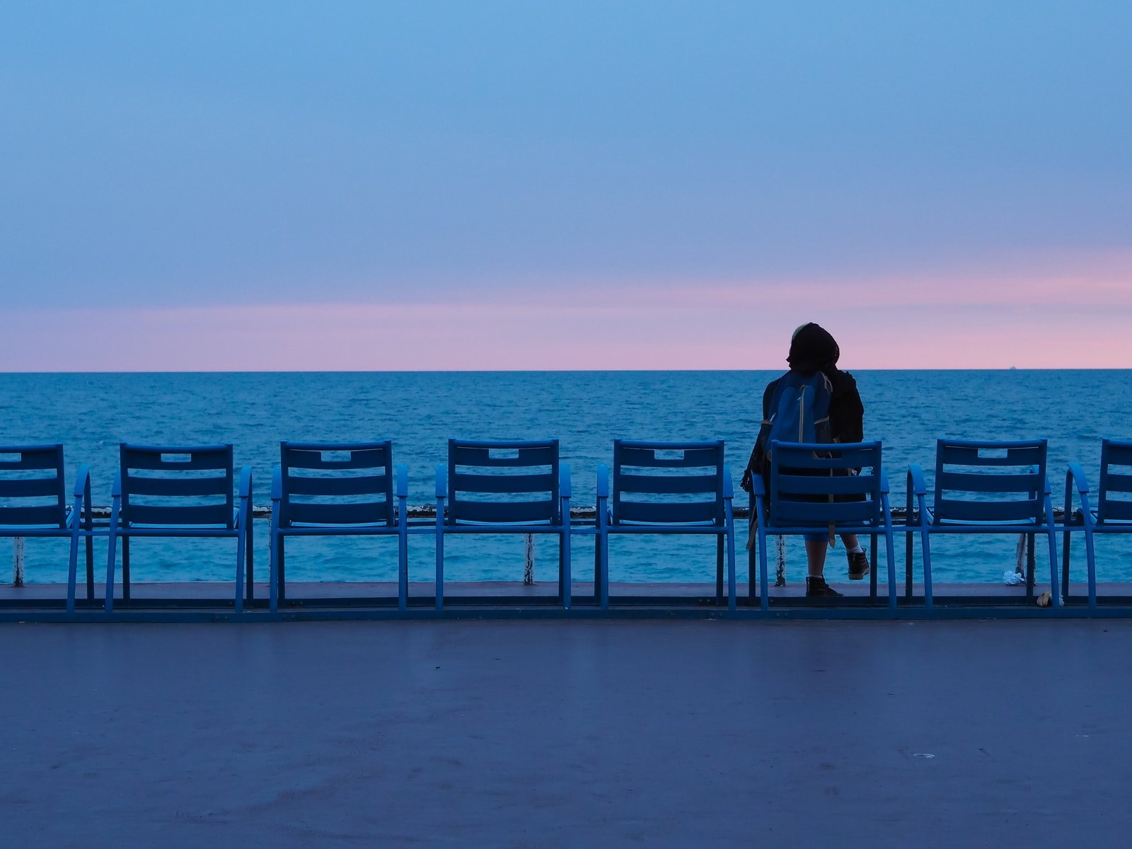 person sitting on blue wooden bench on beach during daytime
