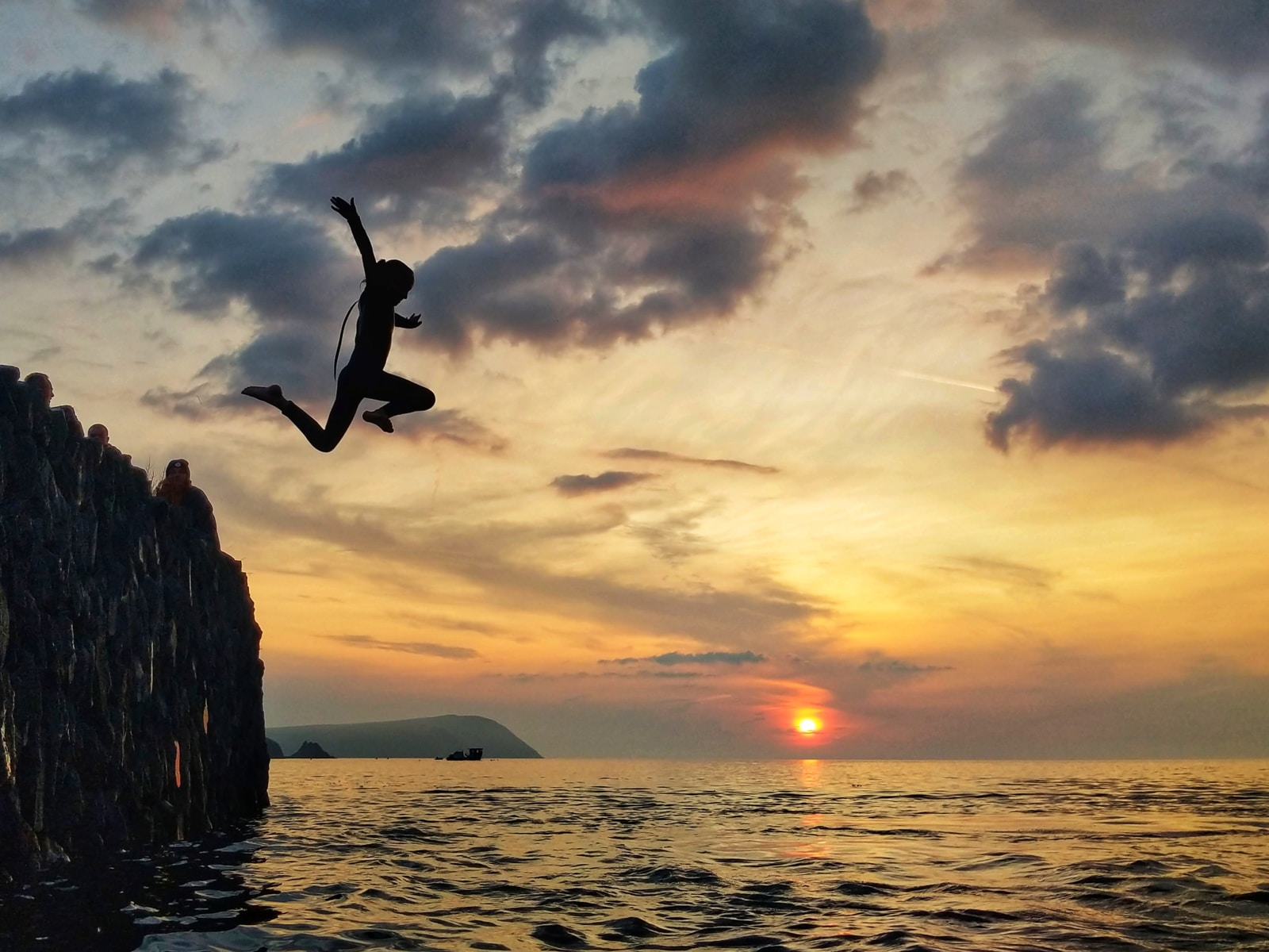 silhouette of man jumping on sea during sunset