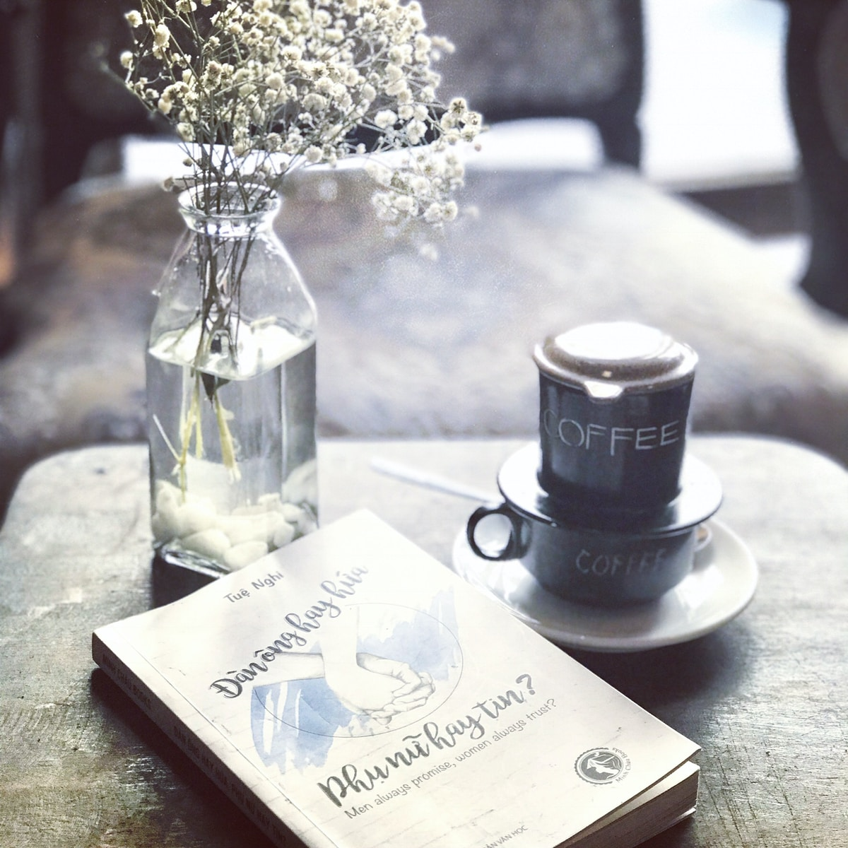 labeled book near teacup and saucer and vase